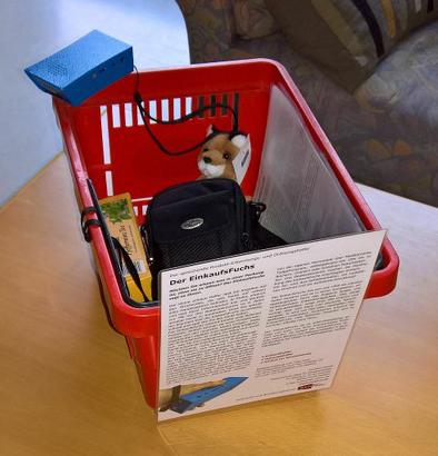Bildbeschreibung: Der EinkaufsFuchs wartet im Einkaufskorb des Forschungsinstitut für Technologie und Behinderung zusammen mit seinem Maskottchen, dem kleinen Plüschfuchs, geduldig auf die nächste Demonstration seiner Produktkenntnisse. (Foto: Michael Hubert)